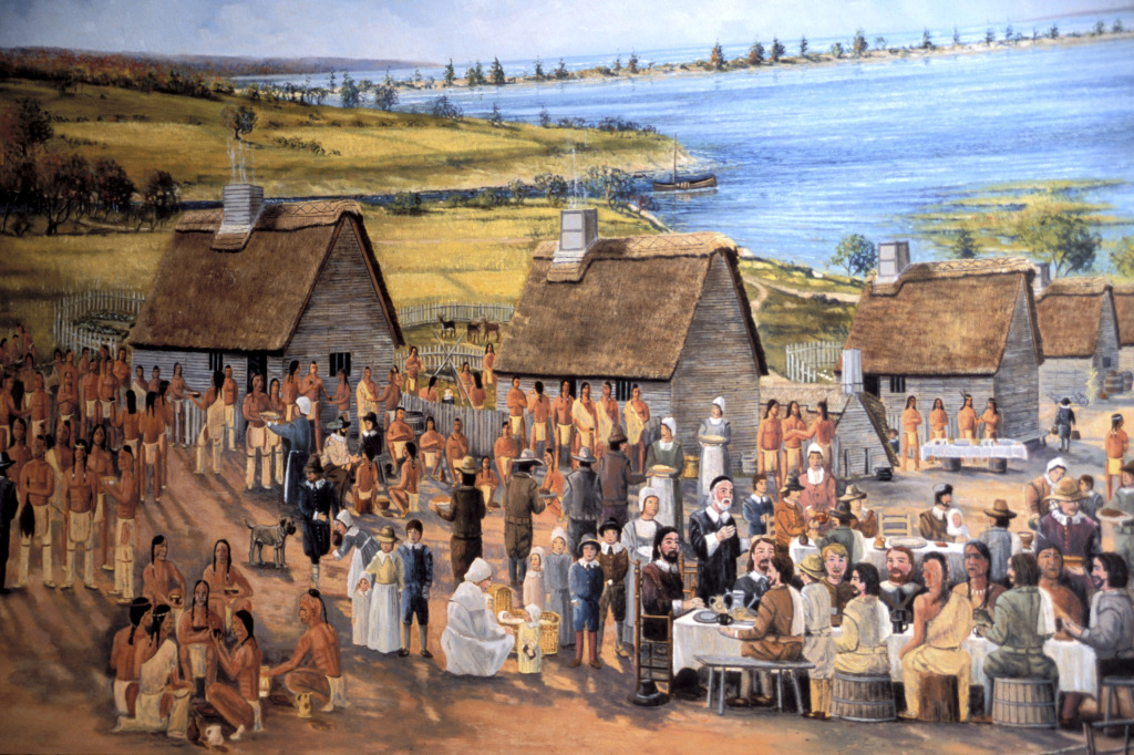Artist's rendering of the first Thanksgiving, 1621. William Bradford, seated at the table, is presiding over the feast in his role as governor.